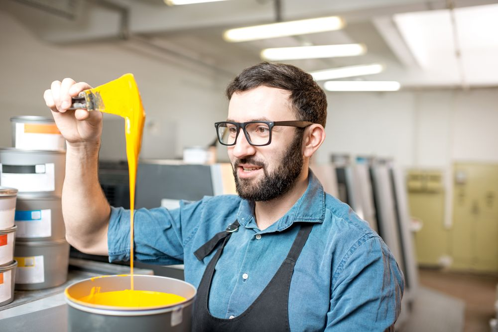 Typographer stiring yellow paint for offset machine standing at the printing manufacturing